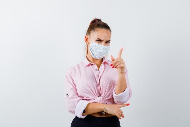 Giovane donna che punta lontano in camicia, pantaloni, mascherina medica e che sembra sicura. vista frontale.