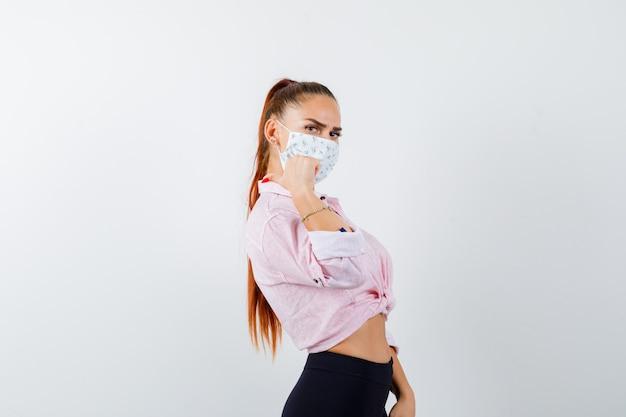 シャツ、ズボン、マスクを親指で後ろを向いて自信を持って見える若い女性。