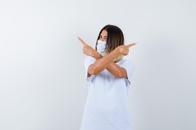 Giovane donna che punta entrambi gli angoli in maglietta, maschera e sguardo esitante. vista frontale.