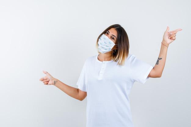 Giovane donna che punta entrambi i lati in t-shirt, maschera e aspetto allegro, vista frontale.