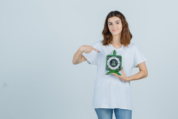 Young female pointing at clock in white t-shirt, jeans and looking cheery. front view.