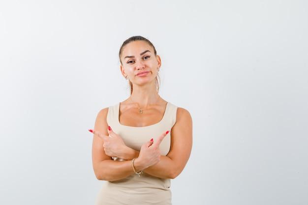 Giovane donna che punta a lati incrociati in canottiera beige e guardando fiducioso, vista frontale.
