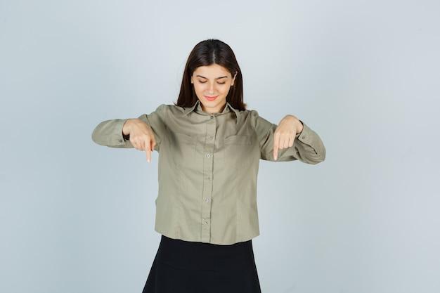Молодая женщина указывает вниз в рубашке, юбке и смотрит с надеждой
