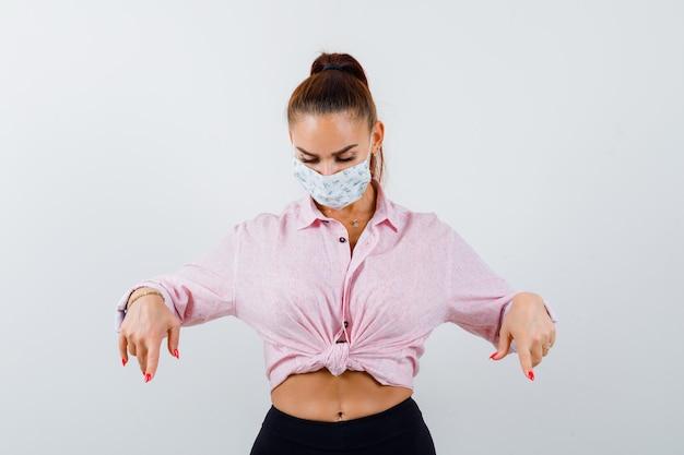 Giovane donna con la punta rivolta verso il basso in camicia, pantaloni, mascherina medica e guardando fiducioso. vista frontale.