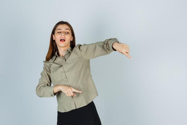 Giovane donna che punta verso il basso in camicia, gonna e sembra concentrata. vista frontale.