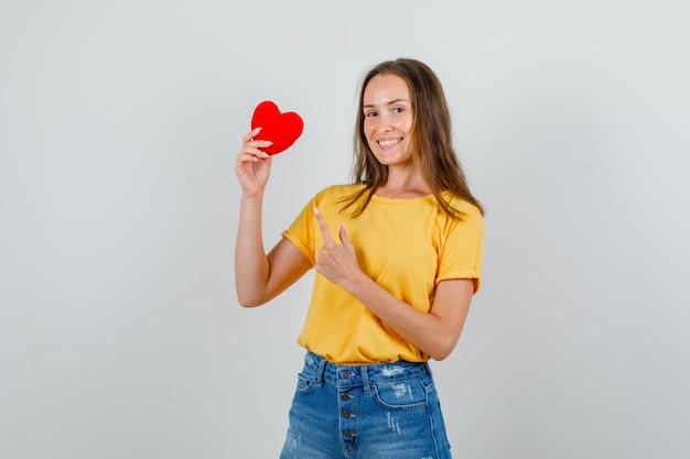 Tシャツ、ショートパンツ、陽気に見える赤いハートに若い女性の人差し指