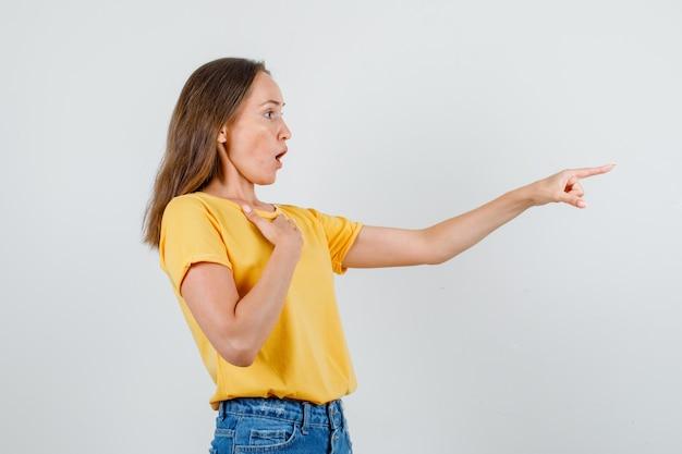 Молодая женщина указывая пальцем вперед с рукой на груди в футболке, вид спереди шорты.