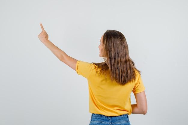 若い女性の人差し指を上に向けて、tシャツ、ショートパンツ、背面図で笑っています。