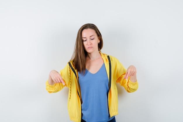 若い女性は、tシャツ、ジャケット、焦点を合わせて、正面図で指を指しています。