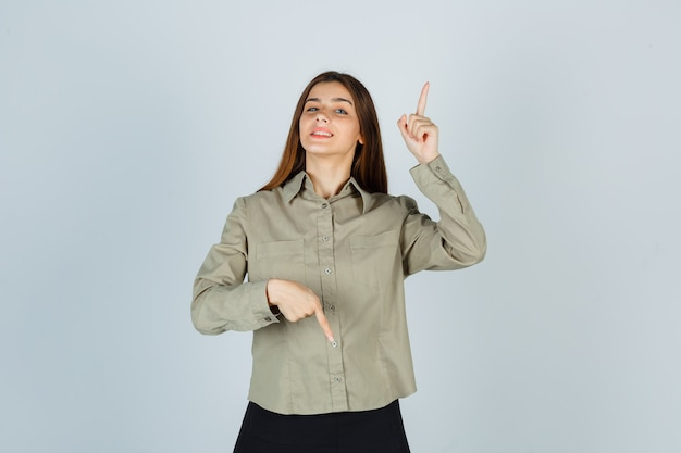 Young female pointing fingers up and down in shirt, skirt and looking proud