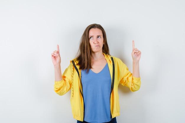 若い女性がtシャツ、ジャケットを着て指を上に向け、躊躇しているように見えます。正面図。