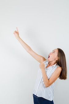 若い女性がtシャツ、ジーンズで指を上に向けて、驚いたように見える、正面図。