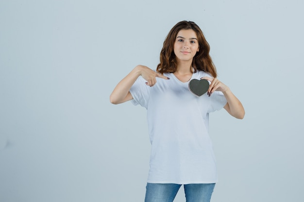 Young female pointing at gift box in white t-shirt, jeans and looking glad. front view.