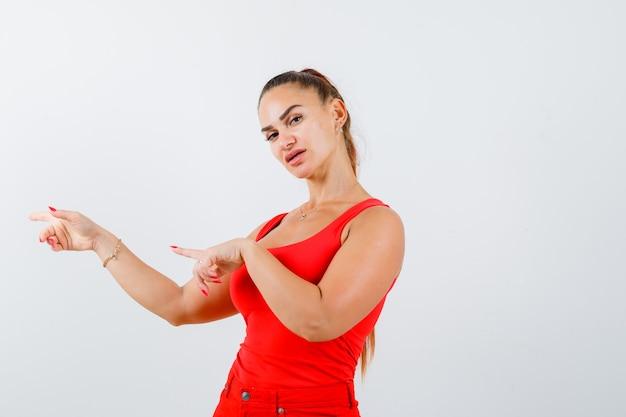 Giovane donna che punta a sinistra in canottiera rossa, pantaloni e guardando fiducioso, vista frontale.