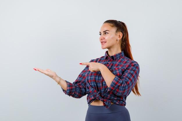 Giovane femmina che indica al palmo in camicia a scacchi, pantaloni e sembra felice. vista frontale.