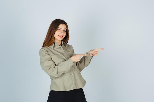 Молодая женщина указывает вправо в рубашке, юбке и выглядит весело