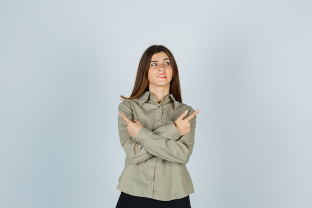 Young female pointing right and left, biting lip, looking up in shirt, skirt and looking forgetful , front view.