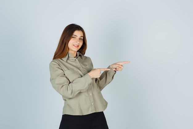 Giovane donna che punta a destra in camicia, gonna e sembra allegra