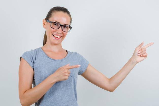 Giovane donna che punta a lato o dà il benvenuto in maglietta grigia, occhiali e sembra felice, vista frontale.