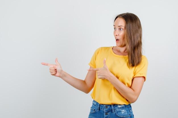 Giovane donna che punta a lato con il gesto della pistola in t-shirt, pantaloncini e cerca allegro