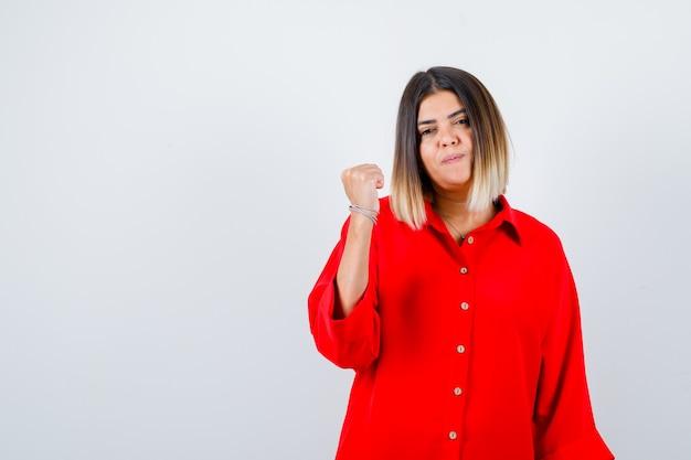 Giovane femmina che indica pollice in su indietro in camicia oversize rossa e sembra sicura. vista frontale.