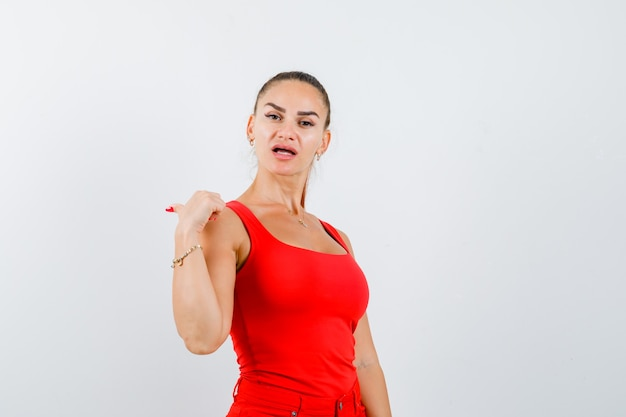 빨간 탱크 탑, 바지와 자신감을 찾고 왼쪽 엄지 손가락을 가리키는 젊은 여성. 전면보기.