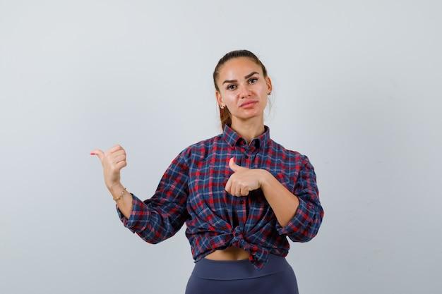 체크무늬 셔츠, 바지를 입고 자신감을 갖고 앞모습을 보고 있는 젊은 여성이 왼쪽을 엄지손가락으로 가리키고 있습니다.