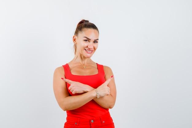 赤いタンクトップ、パンツ、幸せそうに見える、正面図で両側を指している若い女性。