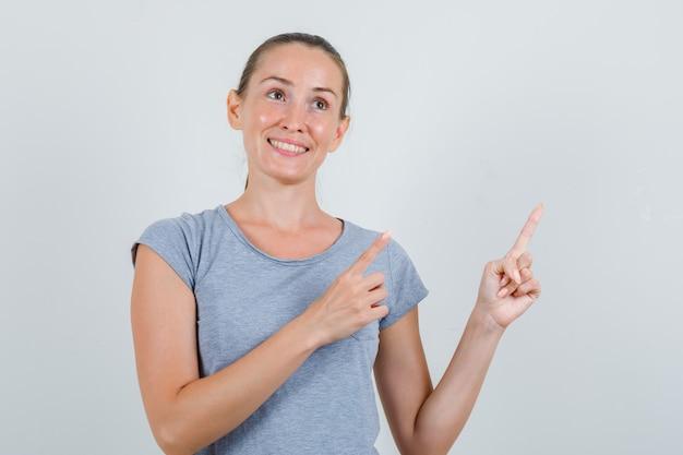 灰色のtシャツで横向きで陽気に見える若い女性、正面図。
