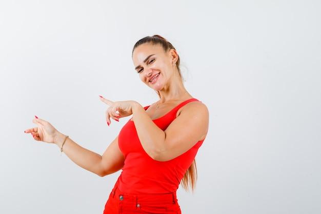 赤いタンクトップ、パンツ、幸せそうに見える左側を指している若い女性。正面図。