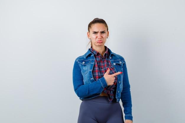 市松模様のシャツ、ジャケット、パンツで右側を指して、気分を害したように見える若い女性、正面図。