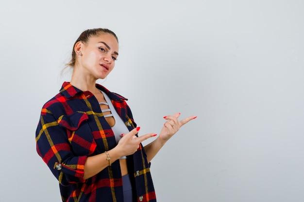 クロップトップの右側を指している若い女性、市松模様のシャツ、自信を持って見えます。正面図。