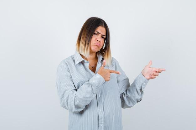 特大のシャツを着て右側を指して、物欲しそうな正面図を見る若い女性。