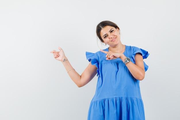 青いドレスを着て横を指して陽気に見える若い女性