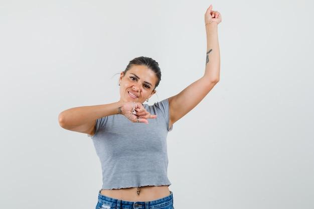 T- 셔츠, 반바지에 손가락으로 측면을 가리키고 귀여운 찾고 젊은 여성.