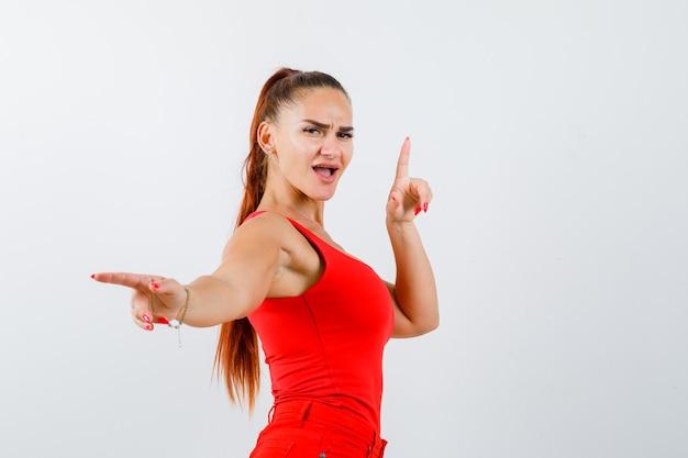赤いタンクトップ、ズボンで上向きと脇を向いて、面白がって見える若い女性。正面図。