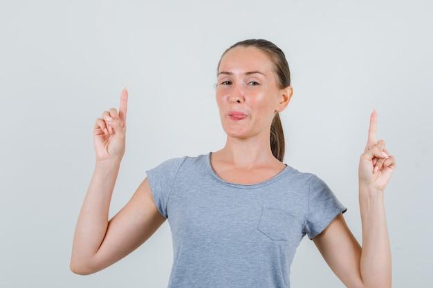 Молодая женщина указывая вверх и показывая язык в серой футболке, вид спереди очки.