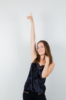 Young female pointing up in black singlet, pants and looking cheerful