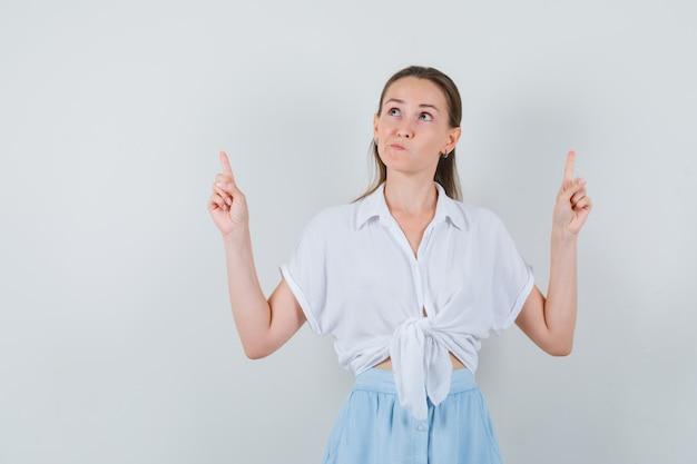 Giovane donna rivolta verso l'alto in camicetta e gonna e che sembra esitante