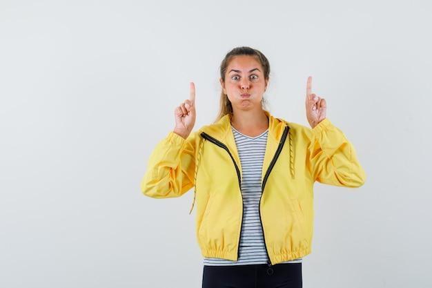 Молодая женщина указывая вверх, надувая щеки в куртке, футболке и выглядела озадаченной. передний план.