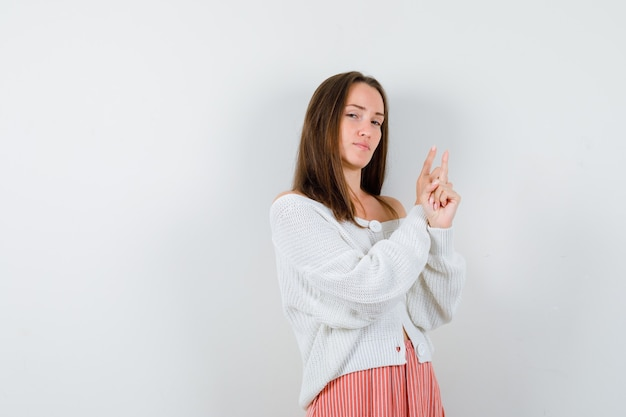 Young female pointing up in cardigan and skirt looking confident isolated