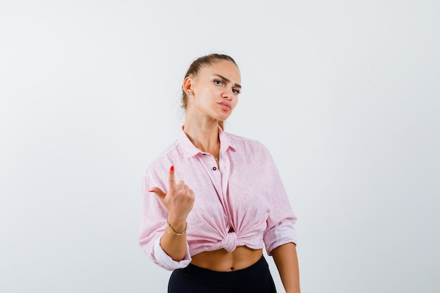Young female pointing up in casual shirt, pants and looking confident