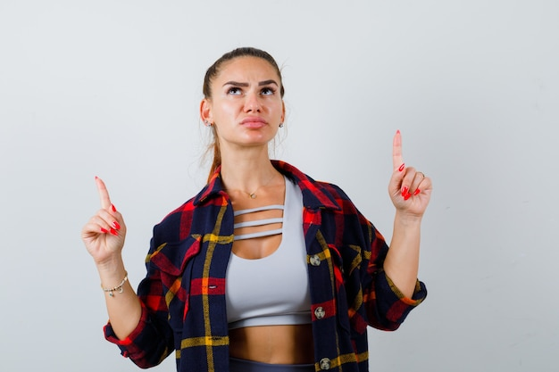 Young female pointing up in checkered shirt, crop top and looking serious. front view.