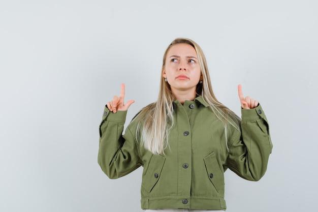 녹색 자 켓에서 가리키는 혼란 스 러 워 보이는 젊은 여성. 전면보기.