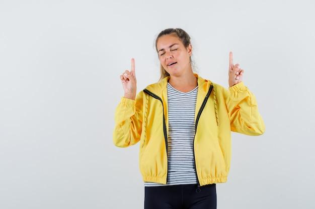 Молодая женщина, указывая вверх в куртке, футболке и выглядит счастливым, вид спереди.
