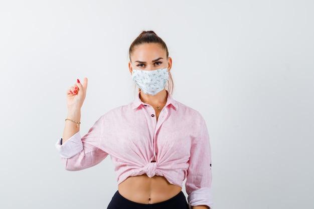 젊은 여성 셔츠, 바지, 의료 마스크를 가리키고 자신감을 찾고. 전면보기.