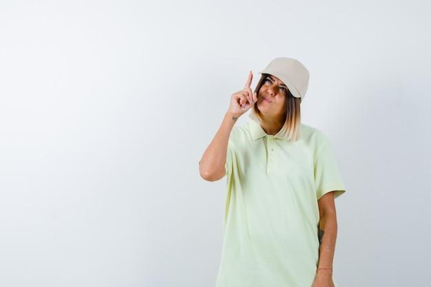 젊은 여성 t- 셔츠, 모자를 가리키고 주저, 전면보기를 찾고.