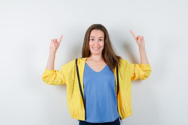 若い女性がtシャツ、ジャケットを上向きに、自信を持って正面から見ています。