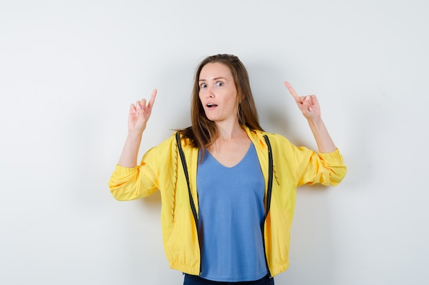 Tシャツ、ジャケット、好奇心旺盛な正面図で上向きの若い女性。
