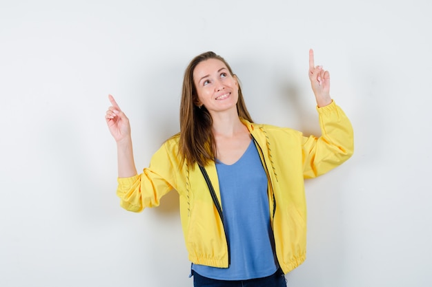 Tシャツ、ジャケットで上向きに、希望に満ちた正面図を探している若い女性。